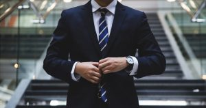 Image of an man in a suit wearing a watch doing up his middle button on his jacket: This article is about Content Marketing