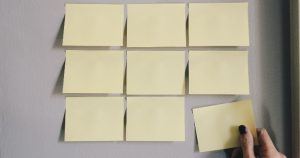Image of someones hand putting post-it notes on a whiteboard: This article is about Content Marketing